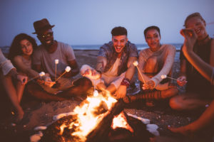 Multi-ethnic hipster friends on summer holidays having fun roasting marshmallows by the sea at dusk