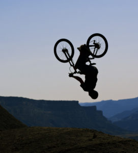 A male mountain bike rider does a back flip off a jump at the end of the day.